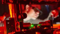"""Der vietnamesische Doktorand Quyet Ngo aus der Forschergruppe """"Photonik in 2D-Materialien"""" untersucht während eines Experimentes am Institut für Angewandte Physik (IAP), Institute of Apllied Physics, der Friedrich-Schiller-Universität Jena in Jena, optische Fasern, die durch zweidimensionale Materialien funktionalisiert wurden. In einer interdisziplinären Zusammenarbeit konnte ein Team aus Jena und Australien zeigen, dass zweidimensionale Halbleiterkristalle direkt auf optischen Fasern wachsen und mit Licht in der Faser wechselwirken. Die Forscher zeigen damit neue Wege zu optischen Fasersensoren und nichtlinearen Lichtkonvertern auf. Foto: Jens Meyer/Universität Jena"""